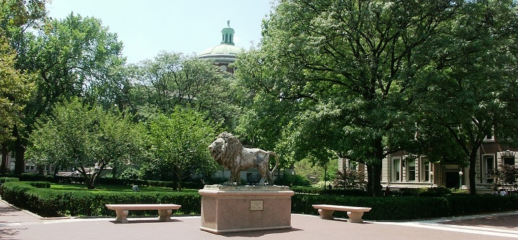 Image of lion statue with trees in the background